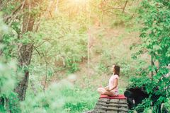 A young woman relaxes in the forest in a yoga pose. Health, sports, nature, fresh air stock photography