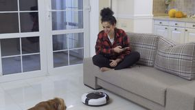Young woman relaxes with phone while the vacuum-cleaning robot clean the floor. Young woman sits at the sofa at home and relaxes with her phone. The vacuum stock video footage