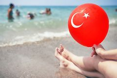 Young woman relaxes on tropical sea beach and holds red balloon with turkish flag on it. Summer vacation on sunny day at sea beach. In Turkey. Legs of girl on Stock Photography