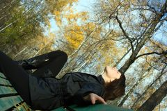 Young woman relaxing. And enjoy life at bench in autumn park Stock Image