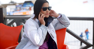 Young woman relaxing at an alpine ski resort Royalty Free Stock Images