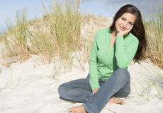 Young woman relaxing amongst dunes Stock Image