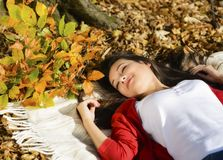 Young woman relaxing in the autumn park Royalty Free Stock Image