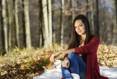 Young woman relaxing in the autumn park Stock Photo