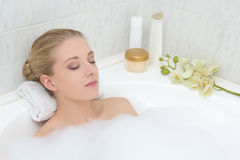Young woman relaxing in bath with foam. Young beautiful woman relaxing in bath with foam Stock Image