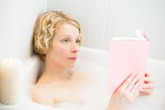 Young woman relaxing in the bath and reading a book Royalty Free Stock Image