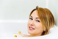 Young woman is relaxing in a bathtube. Portrait of a young woman relaxing in a bathtube stock photography