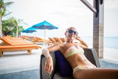 Young woman relaxing at the beach bar. In Indonesia Royalty Free Stock Photography
