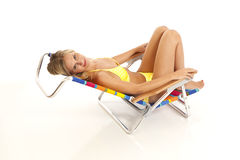 Young woman relaxing in beach chair. Young woman with yellow bikini lying in beach chair Royalty Free Stock Image