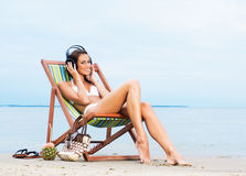 A young woman relaxing on the beach with headphones. Stock Photography