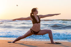 Young woman relaxing on the beach, meditating in warrior asana, at sunset or sunrise and sea Or ocean background, close Royalty Free Stock Photos