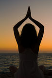 Young woman relaxing on the beach practicing yoga in sunset Royalty Free Stock Photo