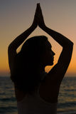 Young woman relaxing on the beach practicing yoga in sunset Stock Photography