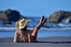 Young woman relaxing on the beach in summer Stock Images
