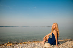 Young woman relaxing at beach on sunny summer morning Stock Photography