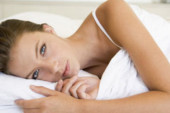 Young woman relaxing in bed. Young woman laying in bed royalty free stock photo