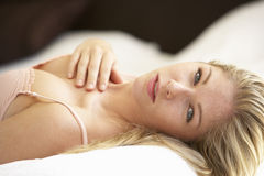 Young Woman Relaxing On Bed Stock Photo