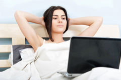 Young woman relaxing in bed with laptop Royalty Free Stock Image
