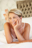 Young Woman Relaxing In Bedroom Stock Photo