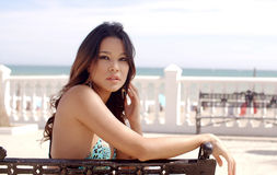Young woman relaxing on a bench at the sea Stock Photo