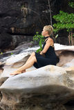 Young woman relaxing on big picturesque rock Stock Images