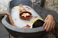 Young woman relaxing in black stone bath with tropical flowers and rose petals. Skin treatment, luxury spa concept royalty free stock photos