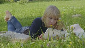 Young caucasian woman relaxing on the blanket in park and uses digital tablet. Young woman is relaxing on blanket in park and uses digital tablet. The female stock video footage