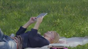 Young woman relax on blanket in park and uses digital tablet. Young woman is relaxing on blanket in park and uses digital tablet. The female enjoys warm weather stock footage