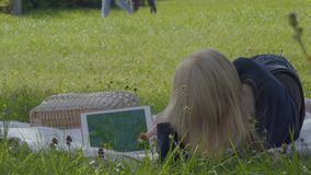 Young woman relaxing on blanket in park and uses digital tablet. Young woman is relaxing on blanket in park and uses digital tablet. The female enjoys warm stock footage