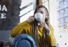 Happy young hipster woman sitting in coffee shop stock photo