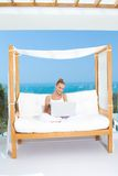 Young woman relaxing on a canopied bench. On a patio overlooking the ocean sitting working with her laptop on her lap Stock Photography
