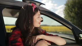 Young woman relaxing on car door during road trip stock footage