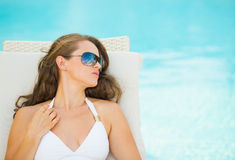 Young woman relaxing on chaise-longue at poolside Royalty Free Stock Photo