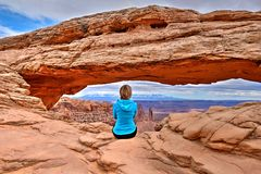 Young woman relaxing on cliff. Mesa Arch in Canyonlands National Park. Moab. Cedar City. Utah. United States Stock Photo