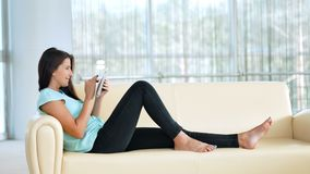 Young woman is relaxing on comfortable couch and using digital tablet indoors.  stock video footage