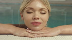 Young woman relaxing at the edge of swimming pool stock footage
