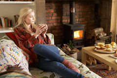 Young woman relaxing by fire. Looking off camera royalty free stock images
