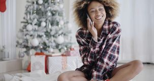 Young woman relaxing in front of a Christmas tree. Young African woman in a trendy outfit sitting on the floor relaxing in front of the Christmas tree chatting stock footage