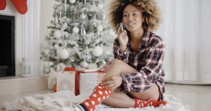 Young woman relaxing in front of a Christmas tree. Young African woman in a trendy outfit sitting on the floor relaxing in front of the Christmas tree chatting stock video