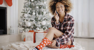 Young woman relaxing in front of a Christmas tree Stock Photography