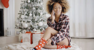 Young woman relaxing in front of a Christmas tree Royalty Free Stock Images