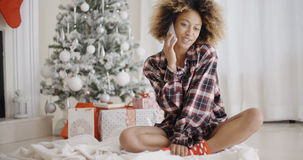 Young woman relaxing in front of a Christmas tree Royalty Free Stock Photos
