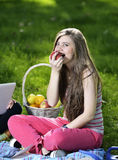 Young woman relaxing on the grass and eating Apples Royalty Free Stock Image