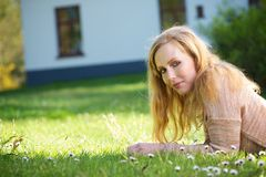 Young woman relaxing on grass outdoors Stock Photo
