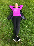 Young woman relaxing on green grass. Athletic young woman relaxing on green grass lying on her back on her jacket with her hands clasped behind her head Stock Image