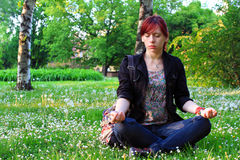 Young woman in a beautiful green park in a relaxing yoga position Royalty Free Stock Photos