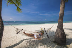 Young woman relaxing in a hammock by the beach Stock Image