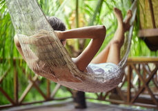 Young woman relaxing in hammock in a tropical resort.back view Stock Images