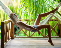 Young woman relaxing in hammock in a tropical resort. Young beautiful woman relaxing in hammock in a tropical resort Royalty Free Stock Photo