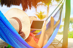 Young woman relaxing in hammockwith touch pad at Royalty Free Stock Images